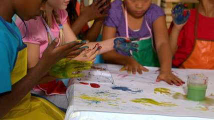 Cute little pupils painting with their hands in classroom