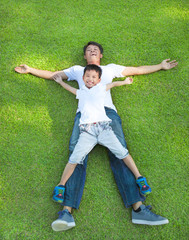 young father and son lying on a meadow together