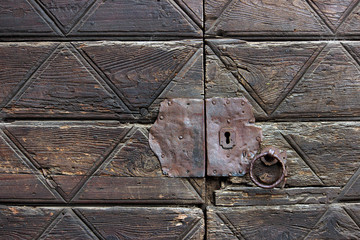 Detail of an old wooden doorway with metal lock and knocker