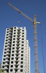 Вершина строящегося жилого дома и башенный кран