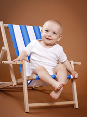 Little cheerful toddler sitting on the sunbed