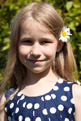 little girl with camomile flower in long hair