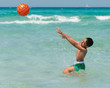 child playing with ball in the turquoise sea