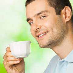 Young smiling man with cup of coffee, outdoors
