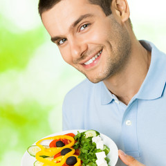 Portrait of smiling man with plate of salad, outdoor