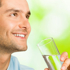 Young smiling man with glass of water, outdoors