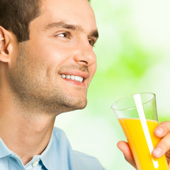 Young smiling man with orange juice, outdoors