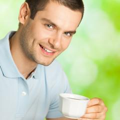 Man drinking coffee, outdoors