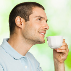 Man drinking coffee, outdoors