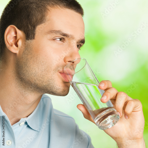 Young man drinking water, outdoors