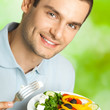 Portrait of young man with plate of salad, outdoor
