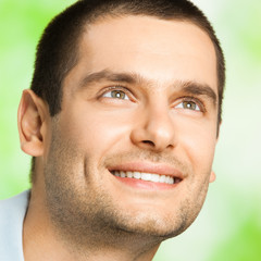 Portrait of young happy man looking up, outdoor