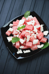 Glass plate with watermelon and feta salad, black wooden surface