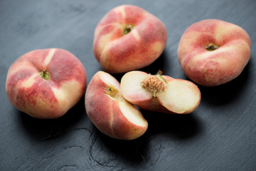 Ripe flat peaches over black wooden surface, studio shot