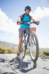 Fit man cycling on rocky terrain