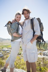 Hiking couple standing on mountain terrain smiling at camera
