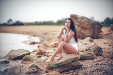 Beautiful young woman on stones near sea