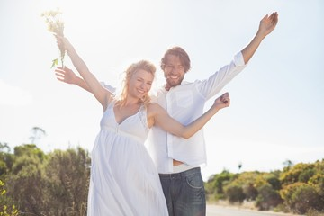 Attractive couple standing with arms raised by the road