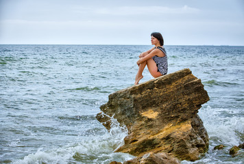woman on rock in beach