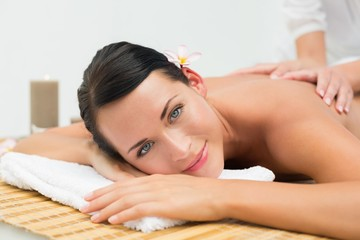 Peaceful brunette enjoying a back massage smiling at camera