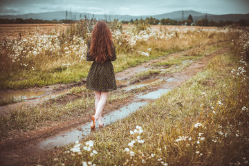 girl going on rural road with a bouquet of wild flowers
