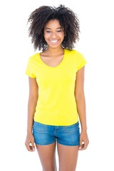 Pretty girl in yellow tshirt and denim hot pants smiling at came
