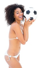 Smiling fit girl in white bikini holding football
