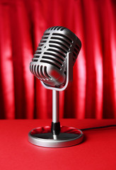 Vintage microphone on table on red cloth background