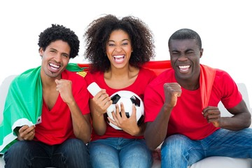 Cheering football fans sitting on couch with portugal flag