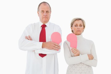 Older couple standing holding broken pink heart