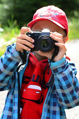 Young boy making photo small camera, outdoor, isolated