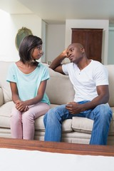 Unhappy couple not talking after argument on sofa