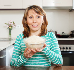 Smiling  woman in green with uncooked rice