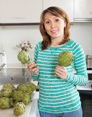 woman  holding artichokes at  kitchen