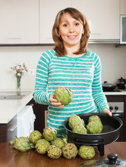 Happy woman cooking artichoke