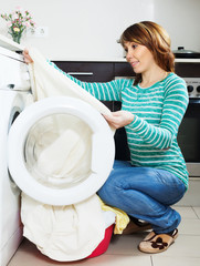 woman cheking  clothes near washing machine