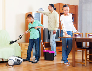 parents with teenage son doing house cleaning