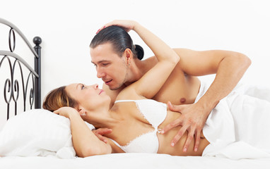 Middle-aged couple awaking together in bed