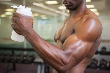 Sporty man holding protein drink in gym