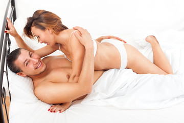 Middle-aged smiling couple kissing and playing on white sheet in