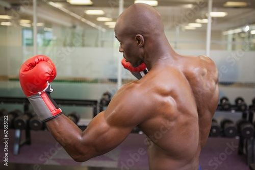 canvas print picture Muscular boxer in defensive stance in health club
