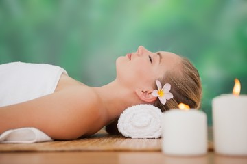 Peaceful blonde lying on bamboo mat with candles