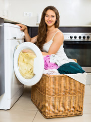 Nice young woman with clothes near washing machine