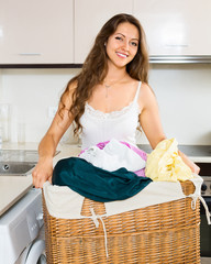 smiling young woman washing clothes in washer