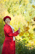 Happy mature woman throwing  maple leaves