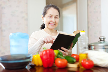 woman  with cookbook in the kitchen