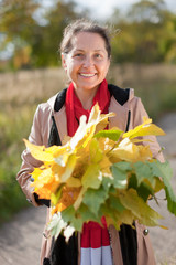 portrait of  happy mature woman with maple posy