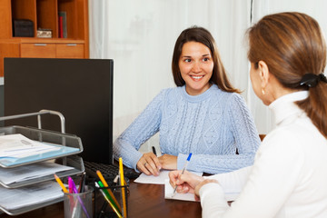 Mature woman answering questions of employee