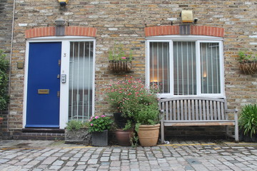 A cosy porch with a blue door, a bench, flowers and two windows