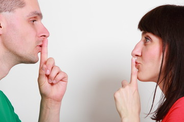 Woman and man showing hand silence sign